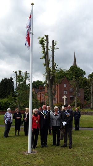 Pictured left to right next to the flagpole are Cllr Spencer, Hamish Wilson, Mary Wilson, and Patrick Smith
